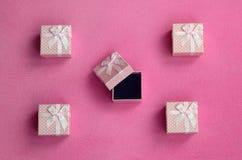 在桃红色颜色的许多小礼物盒与一把小弓在软和毛茸的浅粉红色的羊毛织品毯子说谎  包装g的 免版税库存照片