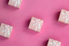 在桃红色颜色的许多小礼物盒与一把小弓在软和毛茸的浅粉红色的羊毛织品毯子说谎  包装g的 库存图片