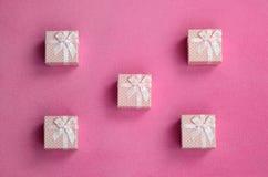 在桃红色颜色的许多小礼物盒与一把小弓在软和毛茸的浅粉红色的羊毛织品毯子说谎  包装g的 免版税库存图片