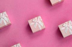 在桃红色颜色的许多小礼物盒与一把小弓在软和毛茸的浅粉红色的羊毛织品毯子说谎  包装g的 免版税图库摄影