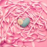 在桃红色颜色装饰缎丝带卷的背景的纺织品心脏  库存照片