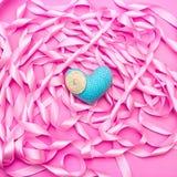 在桃红色颜色装饰缎丝带卷的背景的纺织品心脏  免版税库存照片