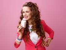 在桃红色饮用的农厂有机酸奶隔绝的微笑的妇女 免版税库存照片