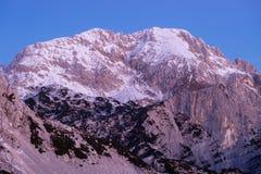 在桃红色黎明光的斯诺伊山顶 图库摄影