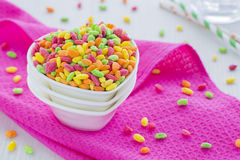 在桃红色洗碗布的五颜六色的米谷物与杯水和秸杆 免版税库存图片