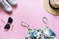 在桃红色backgroud的女性夏天成套装备 有草帽、太阳镜和白色运动鞋的打印的夏天礼服 图库摄影