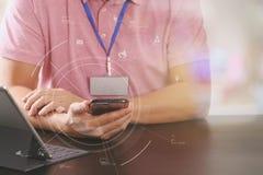在桃红色T恤杉的商人与聪明的电话和digitl一起使用 免版税库存照片