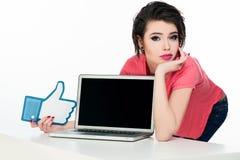 在桃红色T恤杉的年轻模型有在她前面的膝上型计算机的 库存图片