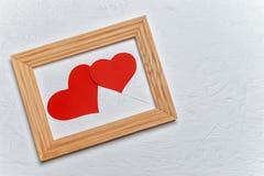 在框架的两红色纸心脏在白色背景 亲人的一件礼物在情人节 免版税库存图片