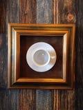 在框架的咖啡杯在moder艺术演示的墙壁上垂悬了 免版税库存照片