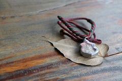在框架的小菩萨护身符与脖子的绳索项链在木桌上的干燥Bodhi叶子 库存图片