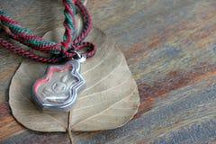 在框架的小菩萨护身符与脖子的绳索项链在木桌上的干燥Bodhi叶子 免版税库存图片