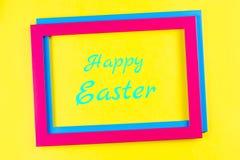 在框架的愉快的复活节贺卡在五颜六色的背景 免版税图库摄影