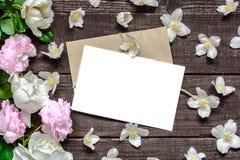 在框架的空白的白色贺卡由桃红色玫瑰和白色茉莉花花制成和信封在土气木背景 库存照片