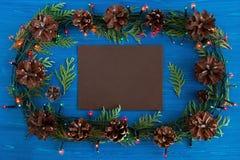 在框架的顶视图从圣诞灯、冷杉分支、杉木锥体和棕色纸片在蓝色木背景的 库存照片