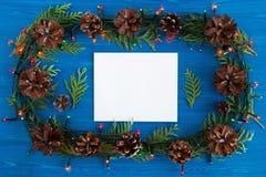 在框架的顶视图从圣诞灯、冷杉分支、杉木锥体和白色纸片在蓝色木背景的 免版税图库摄影