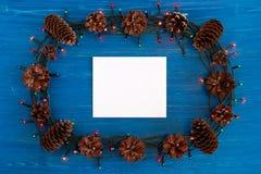 在框架的顶视图从圣诞灯、杉木锥体和白色纸片在蓝色木背景的 库存图片