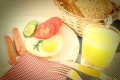 在桌、煎蛋在心形的油煎的香肠,新鲜的切的菜黄瓜和蕃茄,汁液上用早餐 免版税库存照片