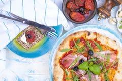 在桌、薄饼和开胃小菜上的意大利食物 家庭晚餐的美丽的服务 橄榄和蓬蒿 干酪和火腿 免版税库存照片