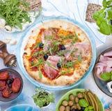 在桌、薄饼和开胃小菜上的意大利食物 家庭晚餐的美丽的服务 橄榄和蓬蒿 干酪和火腿 库存照片