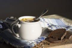 在桌上与装饰品样式和盛汤盖碗的一块蓝色餐巾与黄色汤在阳光下面包木板播种 库存图片