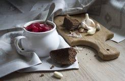 在桌上与装饰品样式的一块蓝色餐巾和盛汤盖碗用在太阳面包大蒜的红色甜菜汤 免版税图库摄影