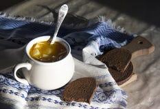 在桌上与装饰品样式的一块蓝色餐巾和盛汤盖碗用在太阳面包的黄色汤 库存照片