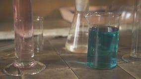 在桌上值得有题字的化工玻璃器皿和玻璃瓶子在拉丁关闭 影视素材