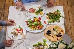 在桌上吃希腊沙拉、海鲜和乳酪盘子的人 免版税库存照片