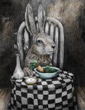 在桌上吃豌豆和红萝卜的艺术兔子 库存图片