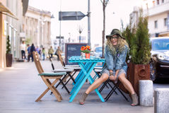 在桌上喝一杯咖啡的疯狂的女孩在城市 免版税库存图片