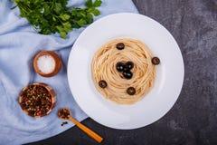 在桌上是一个开胃面团用橄榄、荷兰芹、胡椒混合物和盐罐 免版税库存照片