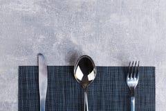在桌上是一把匙子、叉子和刀子在服务餐巾 库存图片