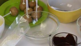 在桌上是在棍子的空白的popcake蛋糕 附近做的流行音乐蛋糕成份 巧克力和五颜六色的选矿 影视素材