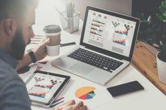 在桌上是有图表、图和图的膝上型计算机和片剂计算机在屏幕,智能手机,纸图表上 回到视图 免版税库存照片