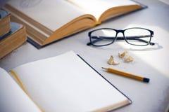 在桌上是百科全书、日志、玻璃、铅笔和削片 免版税库存照片