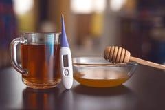 在桌上是茶、温度计、片剂和蜂蜜 库存照片