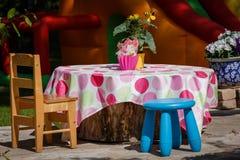 在桌上有一把木椅子和一把蓝色凳子 库存照片