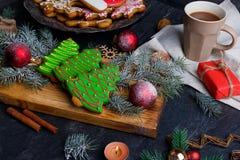 在桌上有圣诞节的一个委员会结块,树,一杯茶的小树枝和圣诞节球 库存照片