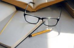在桌上有百科全书、笔记本、铅笔和典雅的玻璃 免版税库存照片