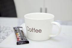 在桌上的一个加奶咖啡杯子 免版税图库摄影