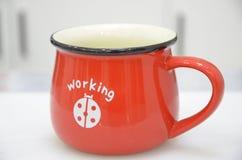 在桌上的一个红色咖啡杯 免版税库存图片