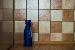 在桌上的一个蓝色瓶在墙壁附近 免版税库存照片