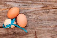 在桌上的三个未加工的鸡鸡蛋 库存图片