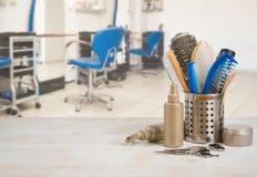 在桌上的专业美发师工具在defocused沙龙内部背景 图库摄影