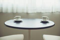 在桌上的两个咖啡杯在窗口早晨附近 库存图片