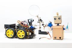 在桌上的两个机器人立场 机器人拿着伺服机和支柱 库存照片