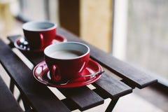 在桌上的两个红色杯子 免版税库存照片