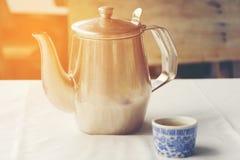 在桌上的中国茶杯和不锈钢茶壶亚洲的街道食物的 库存照片