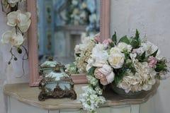 在桌上的人造花花束在卧室 免版税库存图片